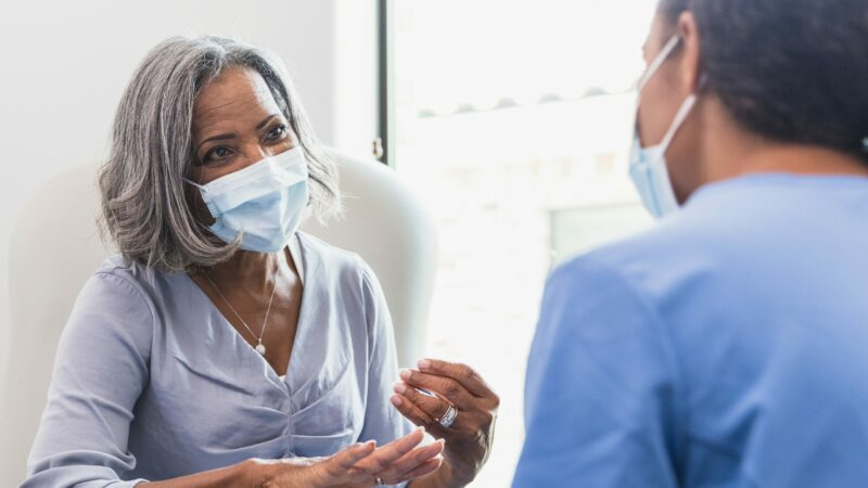 A senior woman, wearing a protective face mask, talks with a female nurse during a medical appointment.